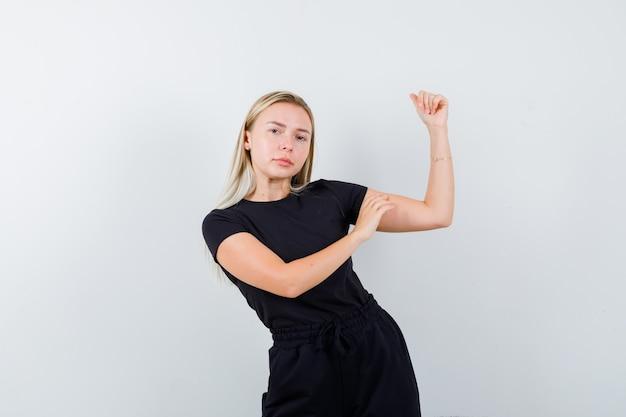 Dame blonde en robe noire montrant les muscles du bras et l'air confiant, vue de face.