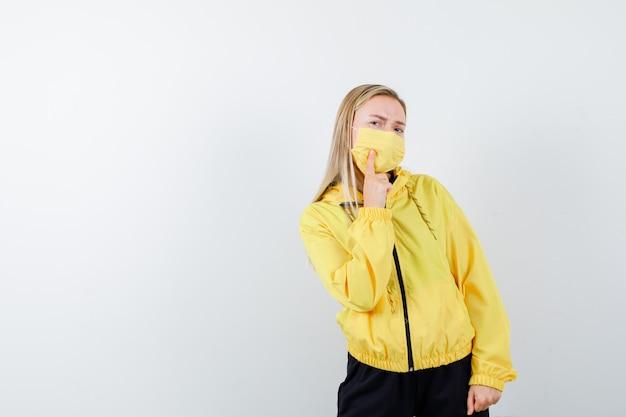 Dame blonde souffrant de maux de dents en survêtement, masque et à la recherche de mal, vue de face.