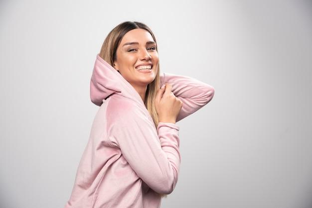 Dame blonde en sweat-shirt rose faisant des poses joyeuses et positives en portant un sweat à capuche sur sa tête.