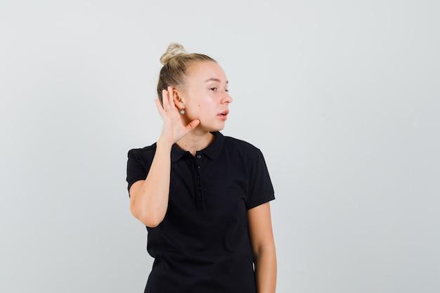 Dame blonde en t-shirt noir tenant la main derrière l'oreille et regardant curieux, vue de face.