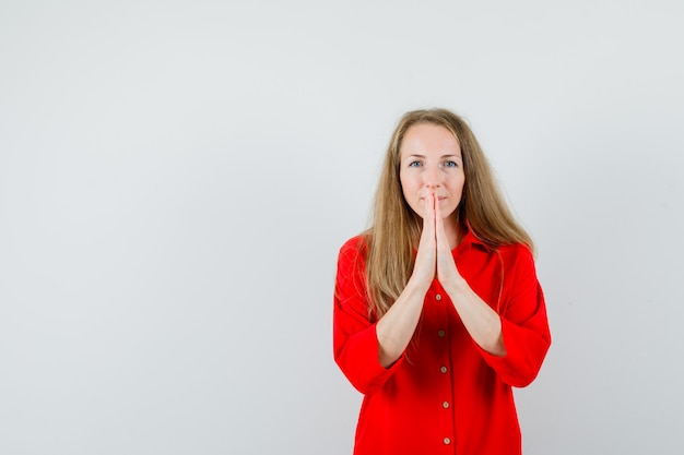 Dame blonde tenant par la main en signe de prière en chemise rouge et à la recherche d'espoir.