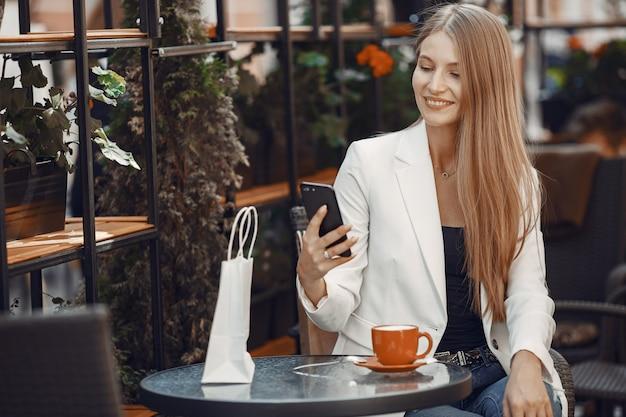 Dame boit un café. femme assise à la table. fille utilise un téléphone.