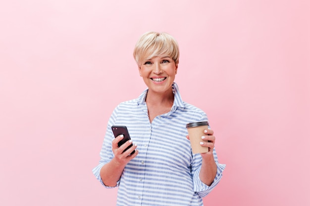 Dame de bonne humeur pose avec tasse à café et téléphone sur fond rose