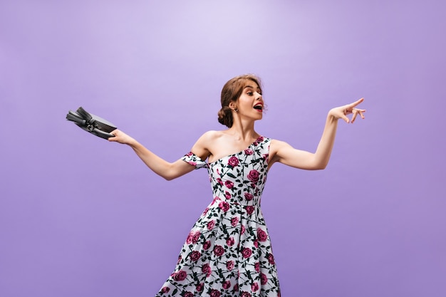 Dame de bonne humeur tient un sac gris sur fond isolé. belle jolie femme en robe à fleurs avec petit sac à main posant.