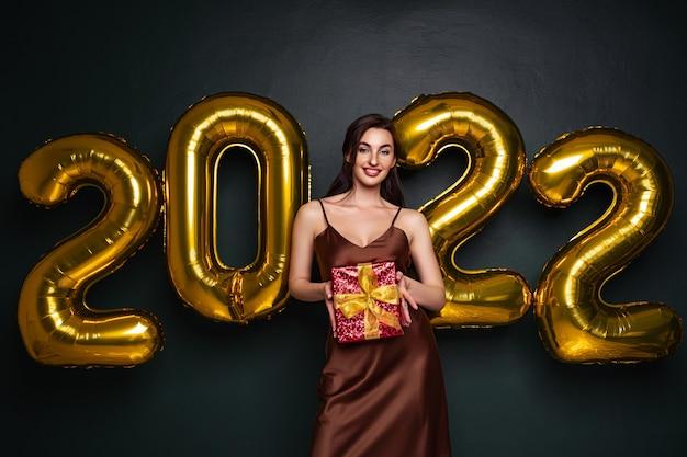 Dame brune georgeous dans une belle robe tenant une boîte-cadeau sur fond de studio noir avec or ...