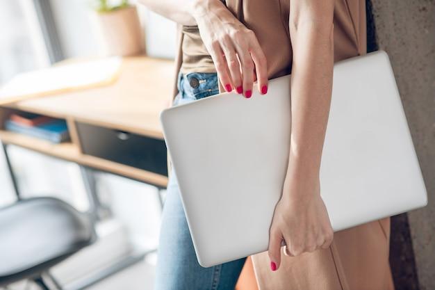 Dame de budiness. gros plan photo de mains féminines tenant un ordinateur portable