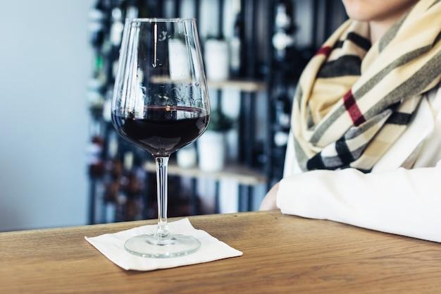 Dame buvant son verre de vin rouge dans un magasin de vins