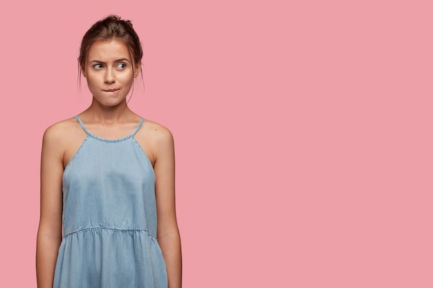 Une dame caucasienne insatisfaite mord les lèvres, regarde avec mécontentement de côté, se sent inquiète, vêtue d'une robe à la mode en denim, se tient contre un mur rose avec un espace libre pour votre texte
