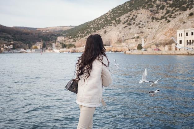 Une dame caucasienne insouciante vêtue de vêtements beiges profitant de la vue sur la mer par une journée chaude et venteuse. femme nourrissant des canards et des mouettes au bord de l'eau dans la ville, la vue de l'arrière.