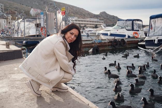 Une dame caucasienne insouciante vêtue de vêtements beiges profitant de la vue sur la mer par une journée chaude et venteuse. femme nourrissant des canards et des mouettes sur le front de mer de la ville