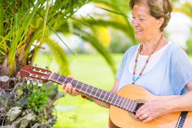 Dame caucasienne mature profiter de l'âge en jouant de la guitare dans les activités de loisirs de plein air sous le soleil