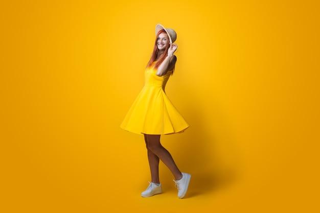 Dame avec chapeau sur la tête et robe jaune posant sur un mur