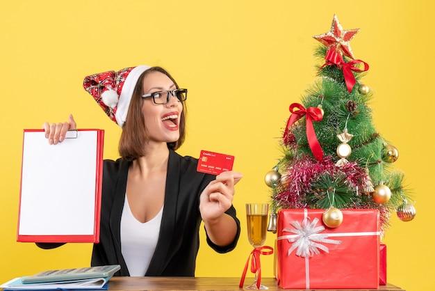 Dame charmante concentrée en costume avec chapeau de père noël et lunettes montrant la carte bancaire et le document au bureau sur jaune isolé