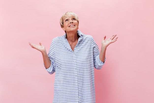 Dame en chemise à carreaux pose avec malentendu sur fond rose