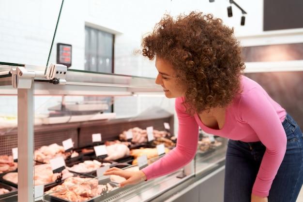 Dame choisissant de la viande crue derrière le comptoir.