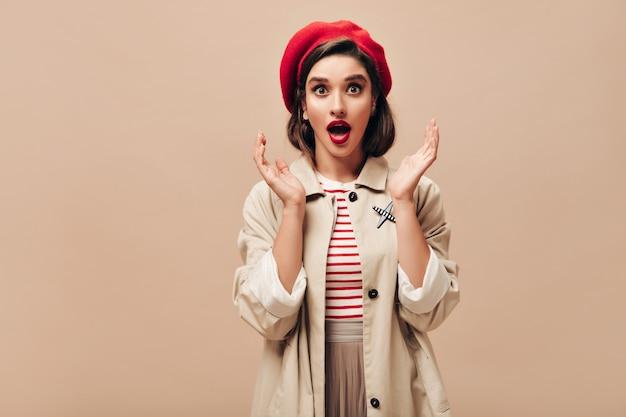 Dame choquée au chapeau rouge et trench beige se penche sur la caméra. fille aux yeux bruns avec des lèvres brillantes dans une tenue élégante pose sur fond isolé.