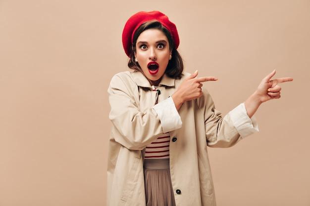 Dame choquée en béret pointant vers la place pour le texte sur fond isolé. femme surprise avec des lèvres brillantes en pull rayé et manteau léger posant.