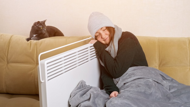 Une dame congelée s'appuie sur un radiateur assis près d'un chat sur un canapé moelleux
