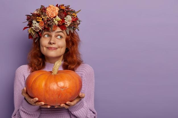 Dame de contenu pensif aux cheveux rouges tient une grosse citrouille mûre