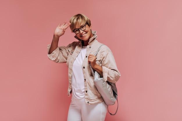 Dame cool positive avec une coiffure blonde et des lunettes modernes dans des vêtements légers souriant et agitant la main sur fond rose isolé.