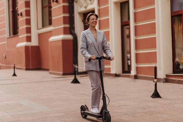 Dame en costume élégant s'amuser et faire du scooter. jolie femme heureuse en veste et pantalon surdimensionnés gris souriant et profitant de la vue sur la ville