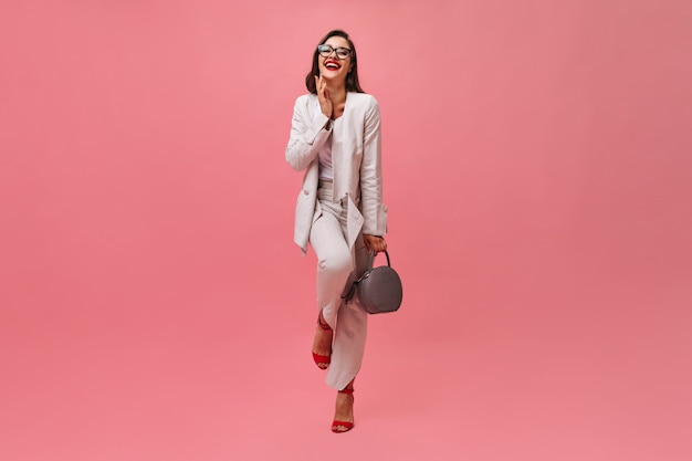 Dame en costume riant et tenant le sac sur fond rose. belle femme d'affaires dans des verres et avec du rouge à lèvres rouge posant à la caméra.