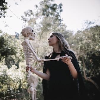 Dame en costume de sorcière attentive au squelette