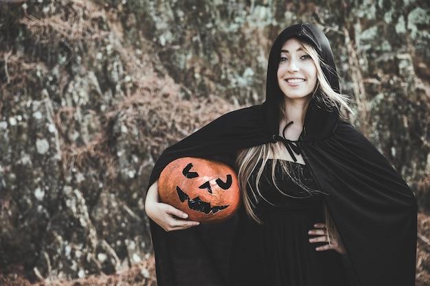 Dame en costume de sorcière avec capuche sur la tête tenant la citrouille