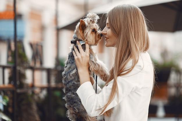 Dame dans un café d'été. femme assise à la table. famale avec un chien mignon.