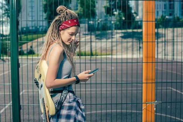 Dame détendue calme debout près de la clôture à mailles de chaîne avec la guitare sur son épaule et regardant l'écran de l'appareil moderne