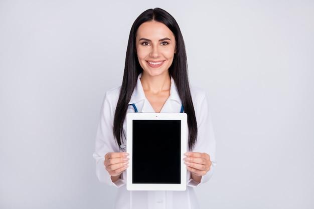Dame de doc professionnel montrant une tablette e-book sur fond de couleur grise
