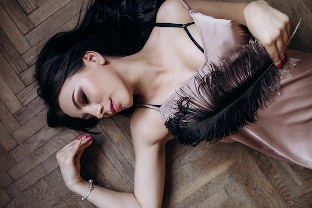 La dame de l'élégance repose sur le sol et garde une plume
