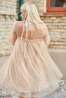 Dame élégante dans une robe beige et des chaussures à talons hauts