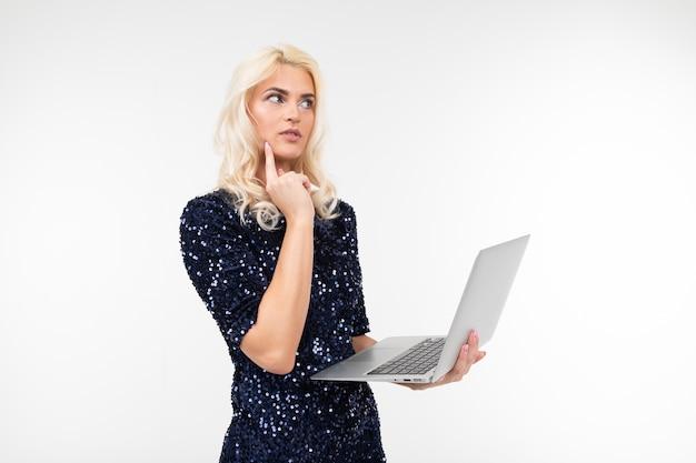 Dame élégante dans une robe bleue brillante tenant un ordinateur portable et en tapant sur un clavier sur fond blanc