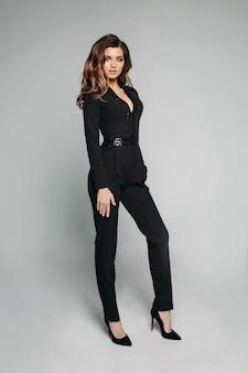 Dame élégante en noir brillant global et talons hauts.