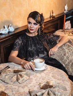Dame élégante à table au restaurant avec une tasse de café.
