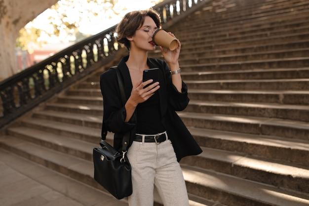 Dame élégante en veste et pantalon blanc buvant du café à l'extérieur. femme aux cheveux courts avec sac et lunettes posant avec téléphone