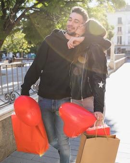 Dame embrassant jeune homme souriant avec des paquets et un ballon dans la rue