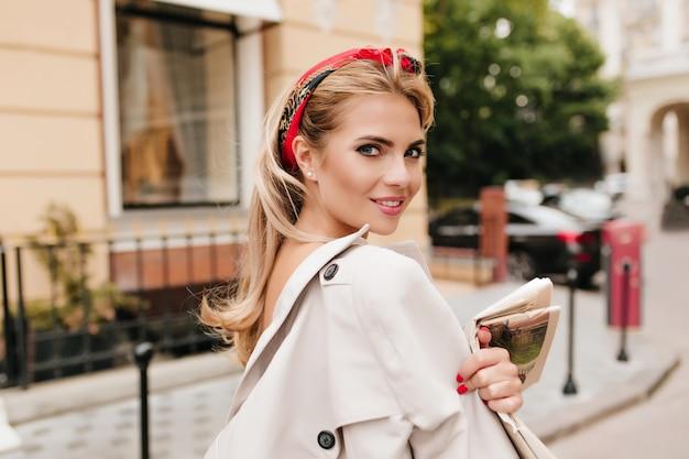Dame enthousiaste avec ruban rouge dans les cheveux blonds regardant par-dessus l'épaule en marchant dans la rue
