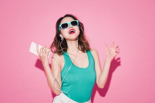 Dame d'été. belle fille asiatique avec maquillage professionnel et coiffure élégante chantant et dansant tout en écoutant de la musique sur fond rose.