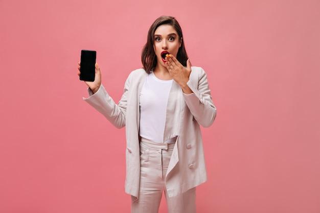 Dame étonnée en costume montre le téléphone sur fond rose. une brune surprise en tenue beige élégante tient le smartphone et pose pour la caméra.