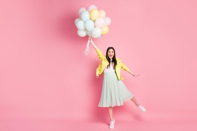 Dame excitée drôle pleine taille tenir la main de nombreux ballons à air qui volent vers le haut