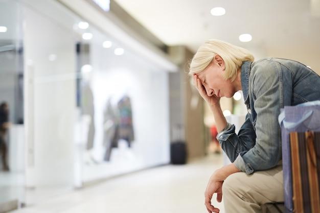 Dame fatiguée du shopping dans le centre commercial