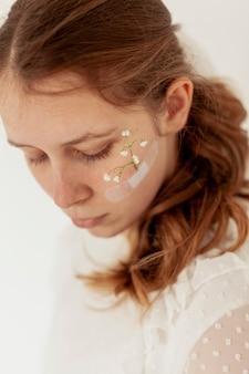 Dame avec des fleurs sur le visage