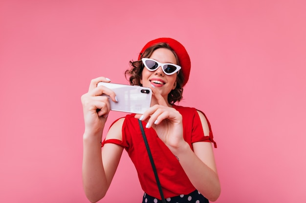 Dame française glamour à lunettes vintage prenant une photo d'elle-même. femme bouclée en béret rouge faisant selfie.
