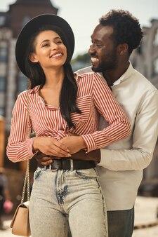 Dame gaie dans un chapeau souriant tandis que petit ami heureux étreignant et mettant les mains sur son ventre