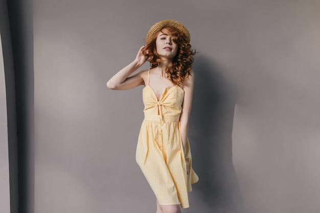 Dame galbée romantique en robe jaune s'amusant à la séance photo. portrait d'adorable fille au gingembre au chapeau isolé sur un mur gris.