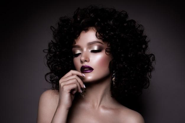 Dame glamour, belle fille sur fond gris. portrait. cheveux ondulés, maquillage parfait. yeux fermés.