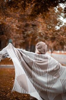 Dame heureuse caucasienne dans des vêtements décontractés chauds et une écharpe confortable dansant et tournant dans le parc en automne