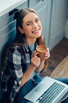 Dame heureuse dans des vêtements décontractés assis sur le sol avec un ordinateur portable et tenant une tasse avec du café